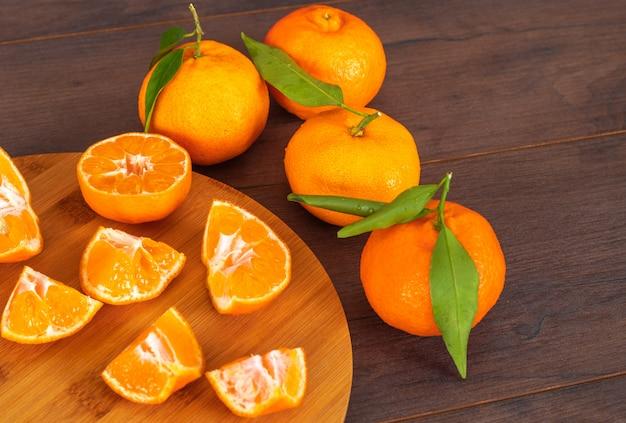 Нарезанные мандарины на разделочной доске с цельными мандаринами на деревянном столе Бесплатные Фотографии