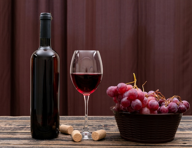Вид сбоку красное вино в бутылке, стакан и виноград на темном столе и горизонтальной Бесплатные Фотографии