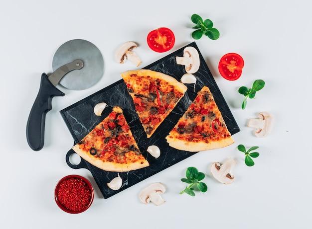 トマトとニンニク、スパイス、マッシュルーム、ミントの葉、フラットな水色の背景にまな板のピザカッターとピザの塊が横たわっていた。 無料写真