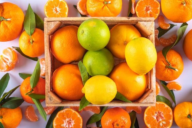 Мандарины лимоны и оранжевые фрукты в деревянной коробке на белой поверхности Бесплатные Фотографии