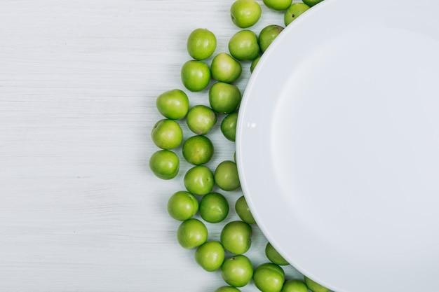 白い木製の背景の空の皿といくつかの緑のチェリープラムクローズアップ。テキストのコピースペース 無料写真