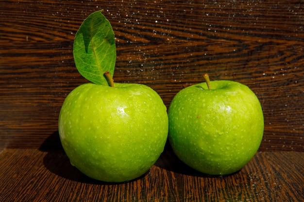 濡れた暗い湾曲した木の葉、葉と涙にぬれた緑のリンゴ。 無料写真