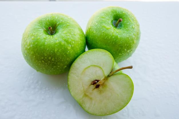 ぬれた青リンゴと白の上半分。閉じる。 無料写真