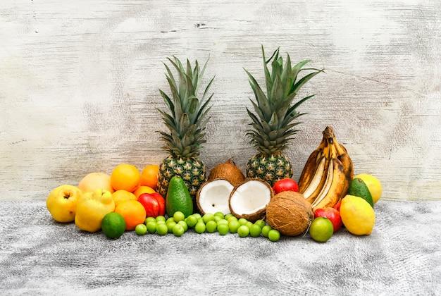 Фруктовый набор из бананов, ананасов, кокосов, авокадо, айвы, персиков, апельсинов, зеленых слив, лимонов на сером гранж и деревянной стене. вид сбоку. Бесплатные Фотографии