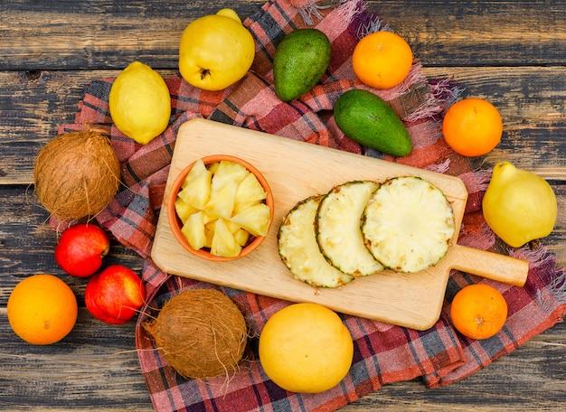 Нарезанный ананас в деревянной доске и миске с кокосами, персиками, айвой и цитрусовыми фруктами сверху на деревянной поверхности гранж и ткань для пикника Бесплатные Фотографии