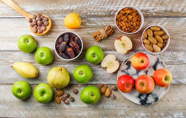 Яблоки и ломтики в тарелке с грушей, палочки корицы, очищенный и неочищенный миндаль в мисках, орехи в деревянной ложке, вид сверху на деревянный Бесплатные Фотографии