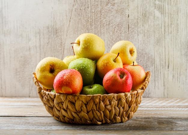 Яблоки с каплями в плетеной корзине на светлых деревянных и гранж Бесплатные Фотографии