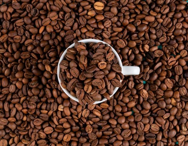 カップの表面を持つトップビューコーヒー豆 無料写真