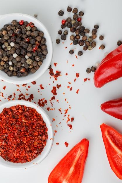 白い壁に唐辛子粉と赤唐辛子のクローズアップとプレートの混合胡椒 無料写真