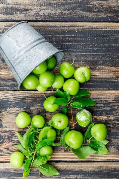 Разбросанные зеленые сливы с листьями, соль от мини ведра на деревянной стене, взгляд сверху. Бесплатные Фотографии