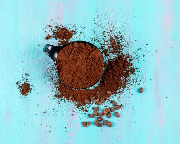Вид сверху молотый кофе в чашке с кофе в зернах на синей поверхности Бесплатные Фотографии
