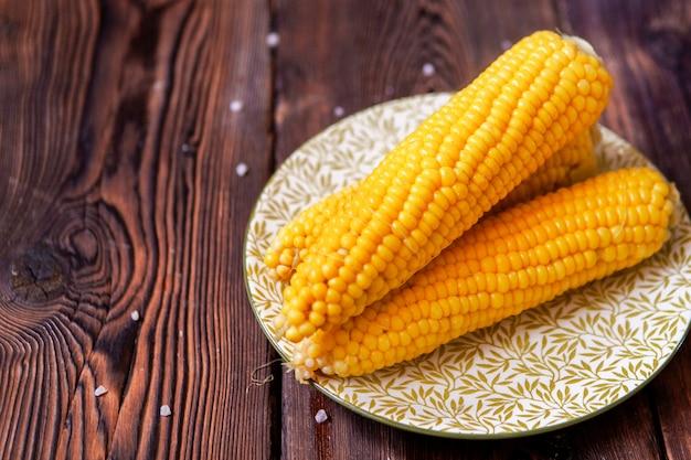 Кукуруза в тарелку на темный деревянный стол. высокий угол обзора. Бесплатные Фотографии