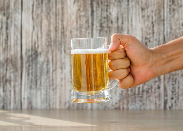 汚れた、ライトテーブル、側面図のガラスのマグでビールを持っている手。 無料写真