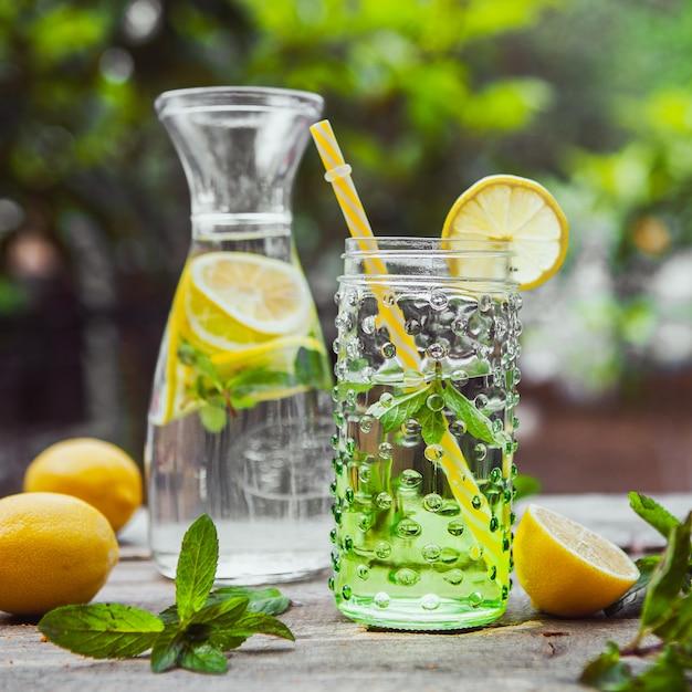 レモネードと成分のガラスの水差しと瓶の木と庭のテーブル、クローズアップ。 無料写真