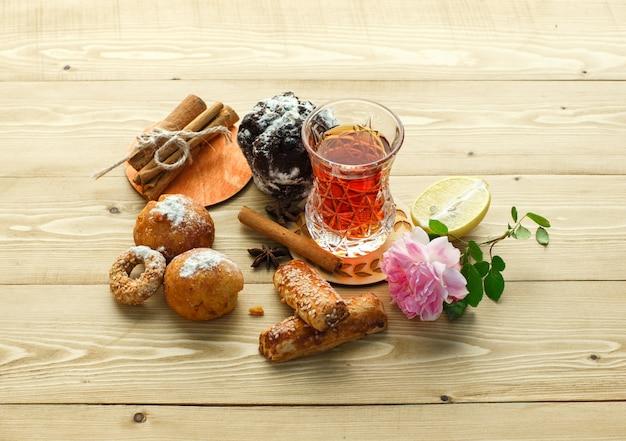 紅茶、シナモンスティック、花、レモン、クローブ、木製の表面、高角度のビューのガラスとビスケット。 無料写真