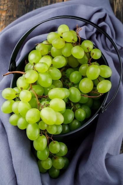 Виноград в ведре на деревянной поверхности. плоская планировка Бесплатные Фотографии