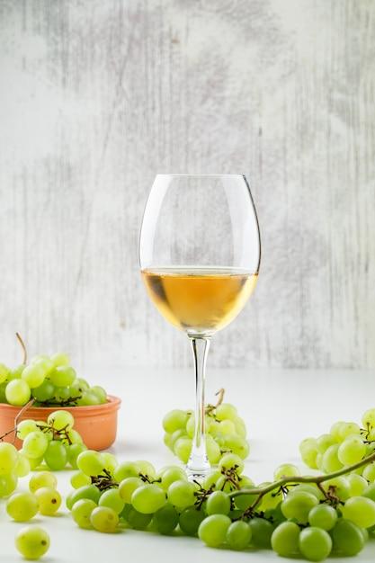 Зеленый виноград с вином в бокале в глиняной тарелке на белой поверхности Бесплатные Фотографии