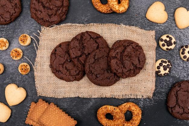 暗い表面に荒布を着たトップビュー異なるクッキー 無料写真