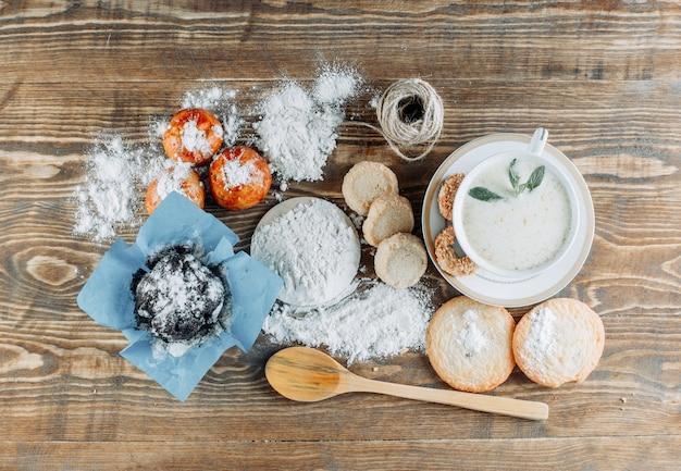 Пряное молоко в чашке с печеньем, ложкой, веревкой, сахарной пудрой сверху на деревянной поверхности Бесплатные Фотографии