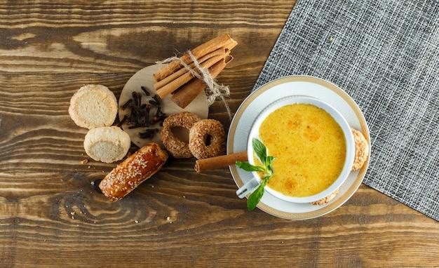 Пряное молоко в чашке с мятой, печенье, гвоздика, палочки корицы вид сверху на деревянный стол Бесплатные Фотографии