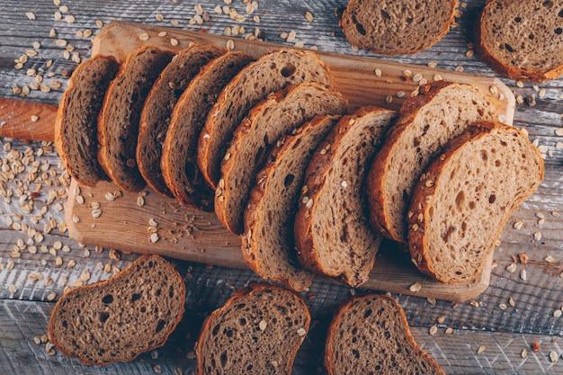 木製の表面、トップビューでまな板の上のいくつかのスライスされたパン 無料写真