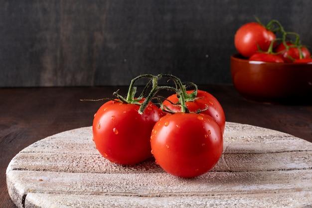 水の滴と木製のまな板有機食品に新鮮なバジルの葉と赤いトマト 無料写真