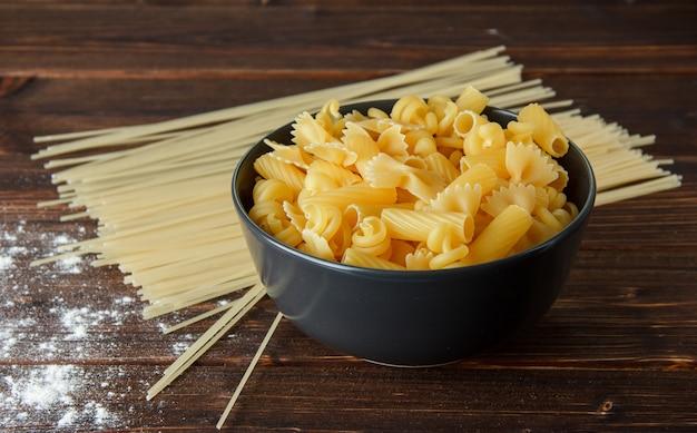 Различные сухие макароны с посыпать мукой на деревянный стол, высокий угол обзора. Бесплатные Фотографии