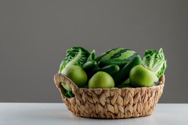 白と灰色のテーブルに籐のかごでレタス、リンゴ、キュウリとスイカ 無料写真