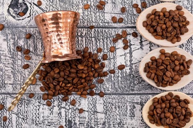 トップビューコーヒー豆コーヒーポットと木製の表面に木製のスプーン 無料写真