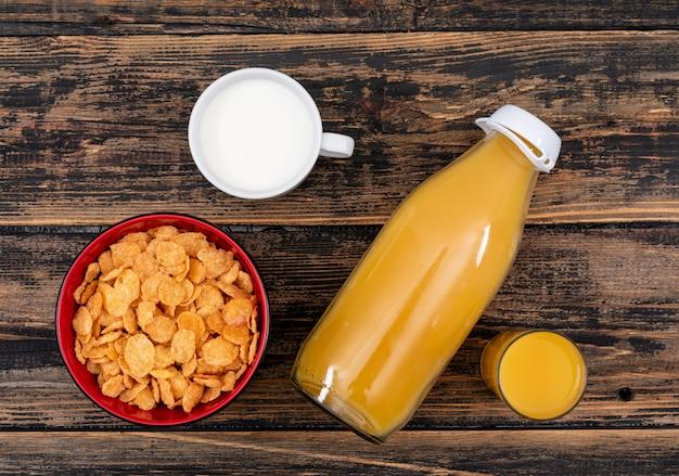 暗い木製の表面の水平にジュースと牛乳とコーンフレークのトップビュー 無料写真