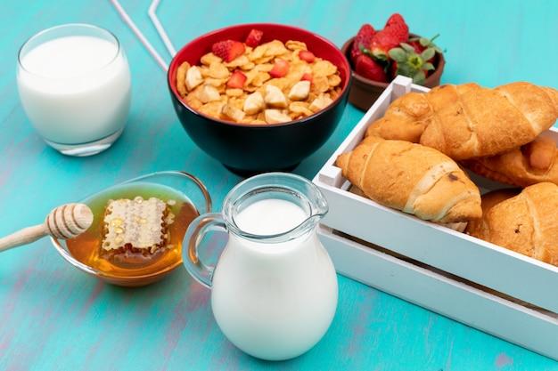 Вид сбоку на завтрак с круассанами, кукурузными хлопьями, фруктами, молоком и медом на синей горизонтальной поверхности Бесплатные Фотографии