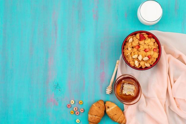Вид сверху завтрак с кукурузными хлопьями, фруктами, молоком и медом с копией пространства на синем фоне горизонтали Бесплатные Фотографии
