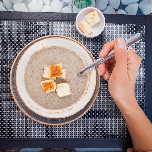 スプーンで石の手で飾られたガラステーブルの上のキノコとトップビューマッシュルームスープ 無料写真