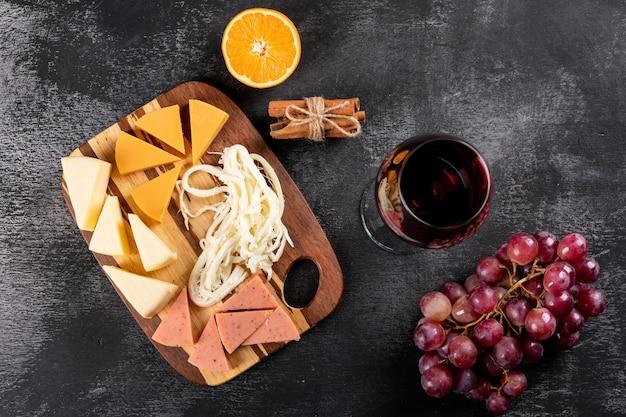 Взгляд сверху красного вина с виноградом, апельсином и сыром на деревянной разделочной доске на темной горизонтальной поверхности Бесплатные Фотографии