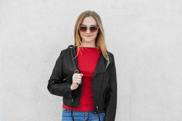 大きなトレンディなサングラス、赤いセーター、ジーンズ、革のコートでおしゃれな若い女性 無料写真