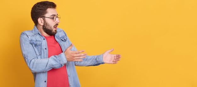先を見据え、腕を上げ、表情を印象付け、口と目を大きく開いた感情的なカリスマ的な男の横顔 無料写真