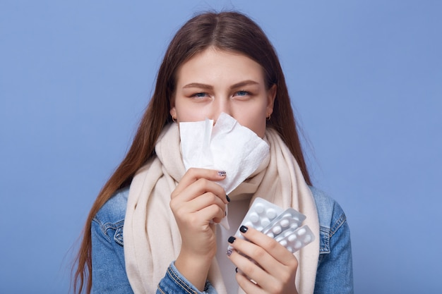 Портрет молодой женщины простуды и держит в руках таблетки Бесплатные Фотографии