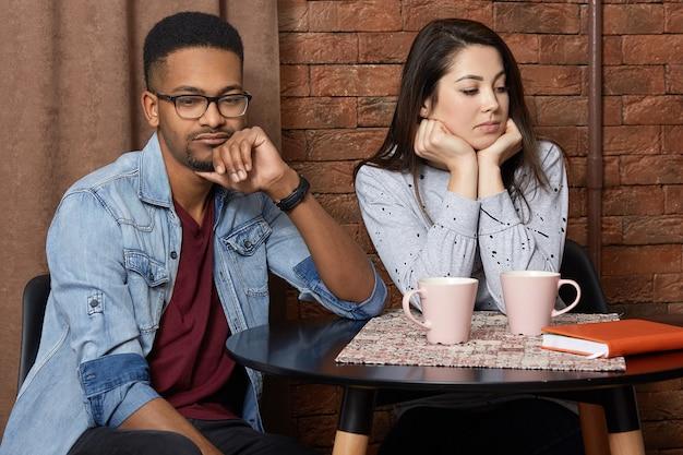 混血の若いカップルは、カフェテリアで口論をし、表情を不快にし、関係を整理し、ホットコーヒーを飲み、お互いに話してはいけません。レストランで不幸な多民族の愛好家。 Premium写真