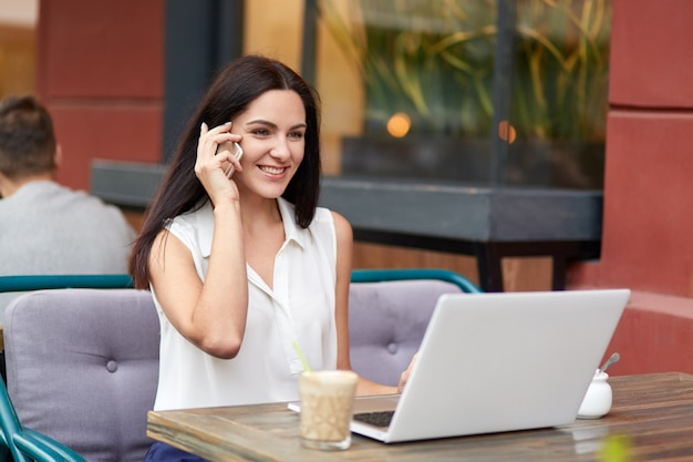 正装の肯定的な女性実業家、電話での会話、同僚との会話、ラップトップコンピューターを使用したビジネスレポート Premium写真
