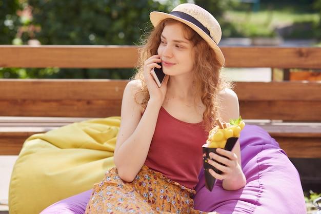 お手玉でポーズ、電話で話している、会話をしている、よそ見、デザートを持っている、赤いトップ、麦わら帽子とカラフルなスカートを着て、気分が良い、喜んでいるほっそりしたモデルの画像。 Premium写真
