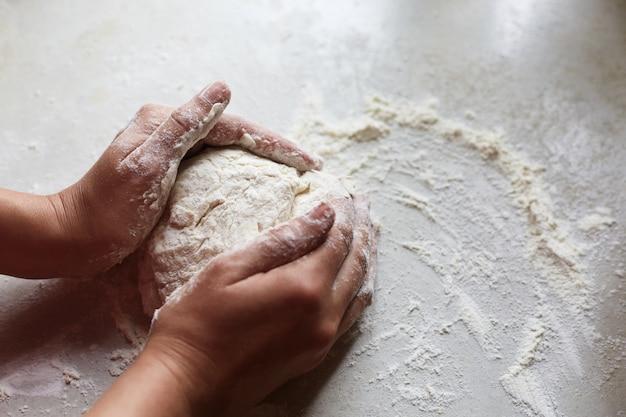 Неизвестные женские руки делают тесто для выпечки, на муке на белом столе хватает муки, отрабатывают навыки выпечки, проводят свободное время на кухне, придают форму выпечке. Premium Фотографии
