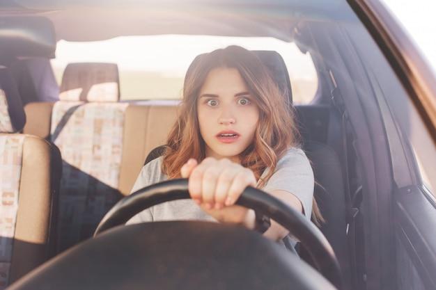 車を運転する前に恐怖の表情が落ち込んでいる恐ろしい若いかわいい女性のルックスは、他の交通機関との衝突や道路での事故に遭い、経験の浅い運転手です。道路上の問題 Premium写真