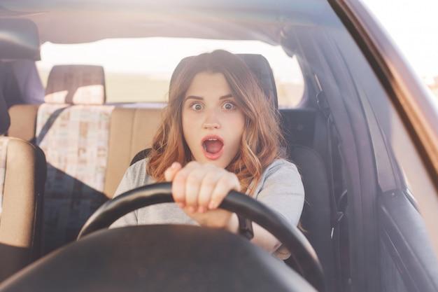 ショックを受けた美しいヨーロッパの女性ドライバーは、自分の車が壊れていること、自分で修理できないこと、路上でのひどい事故を見て、予想外に驚いた怖い表情をしていることに気づきました。運転と問題 Premium写真