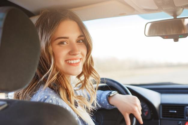 Крупным планом портрет приятной на вид женщины с радостным позитивным выражением, довольной незабываемым путешествием на машине, садящейся на сиденье водителя, наслаждающейся музыкой. Premium Фотографии