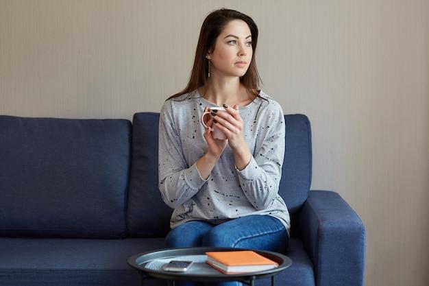 カジュアルなジャンパーとジーンズに身を包んだ、思いやりのあるきれいな女性は脇に焦点を当て、ホットドリンクのマグカップを保持している、モダンなアパートメントのソファーに座っている、スマートフォンとメモ帳付きのコーヒーテーブル、深く考える Premium写真