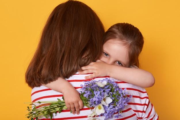 美しい若い女性と彼女の魅力的な小さな娘が屋内を抱き締めます。子供は母の日でお母さんを祝福し、花を贈り、ミイラはストライプのシャツを着て後ろ向きに立ちます。 Premium写真