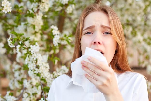 Наружный выстрел недовольства у молодой девушки есть сезонная аллергия, она использует ткани, позирует на цветущем дереве, страдает насморком и чиханием, реагирует на аллергены. горизонтальный вид. концепция людей и болезней Premium Фотографии