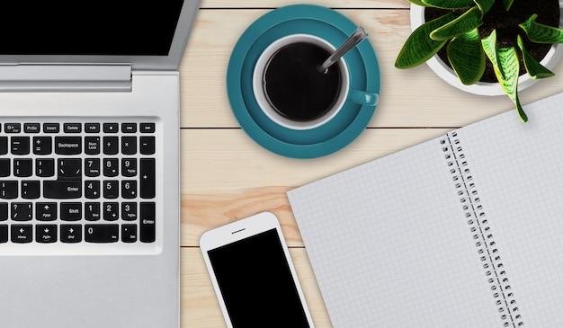Деревянный рабочий стол с предметами, необходимыми для работы. современный ноутбук, смартфон, чашка кофе и блокнот с пустыми листами, лежа на деревянный стол. домашнее рабочее пространство. концепция образования или бизнеса. приборы Premium Фотографии