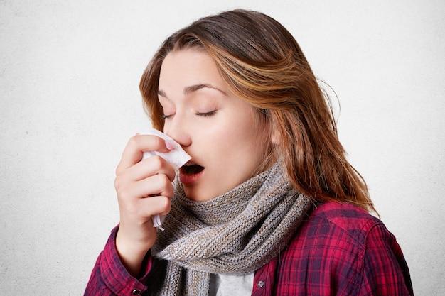 Боком портрет молодой женщины имеет аллергический ринит, чихает в салфетку, имеет головную боль, носит шарф на шее, изолированных на белой стене. болезнь, сезонный вирус и концепция проблемы со здоровьем Premium Фотографии