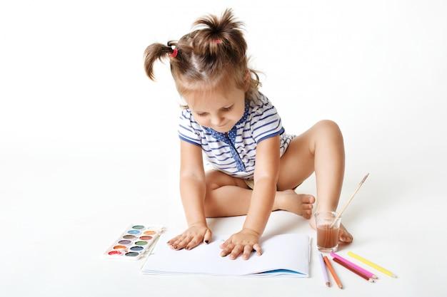 Маленькая очаровательная девушка дошкольника с нарисованными руками, делает отпечатки пальцев на пустой странице альбома, использует акварель для создания картины, будучи очень креативной, изолированной над белой студийной стеной Бесплатные Фотографии